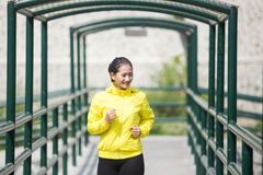 Young asian woman exercising outdoor in yellow neon jacket, jogging Stock Image