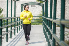 Young asian woman exercising outdoor in yellow neon jacket, jogging Stock Photography