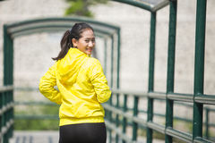 Young asian woman exercising outdoor in yellow neon jacket Royalty Free Stock Photos