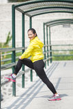 Young asian woman exercising outdoor in yellow neon jacket, stre. A portrait of a young asian woman stretching outdoor in yellow neon jacket Royalty Free Stock Photography