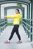 Young asian woman exercising outdoor in yellow neon jacket, stre. A portrait of a young asian woman exercising outdoor in yellow neon jacket, stretching Stock Photos