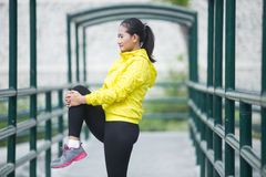Young asian woman exercising outdoor in yellow neon jacket, stre. A portrait of a young asian woman exercising outdoor in yellow neon jacket, stretching Royalty Free Stock Images
