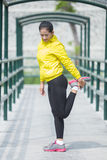 Young asian woman exercising outdoor in yellow neon jacket, stre. A portrait of a young asian woman exercising outdoor in yellow neon jacket, stretching Royalty Free Stock Photos