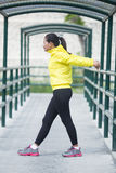 Young asian woman exercising outdoor in yellow neon jacket, stre. A portrait of a young asian woman exercising outdoor in yellow neon jacket, stretching Stock Photo