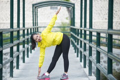 Young asian woman exercising outdoor in yellow neon jacket, stre. A portrait of a young asian woman exercising outdoor in yellow neon jacket, stretching Royalty Free Stock Image