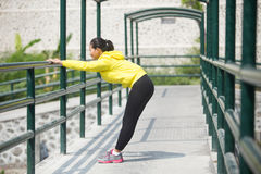 Young asian woman exercising outdoor in yellow neon jacket, stre. A portrait of a young asian woman exercising outdoor in yellow neon jacket, stretching Stock Photography