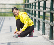 Young asian woman exercising outdoor in yellow neon jacket, tyin. A portrait of a young asian woman exercising outdoor in yellow neon jacket, tying her shoelace Stock Photo