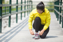 Young asian woman exercising outdoor in yellow neon jacket, tyin. A portrait of a young asian woman exercising outdoor in yellow neon jacket, tying her shoelace Stock Image
