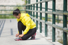 Young asian woman exercising outdoor in yellow neon jacket, tyin. A portrait of a young asian woman exercising outdoor in yellow neon jacket, tying her shoelace Royalty Free Stock Image