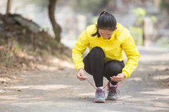 Young asian woman exercising outdoor in yellow neon jacket, tyin. A portrait of a young asian woman exercising outdoor in yellow neon jacket, tying her shoelace Royalty Free Stock Images