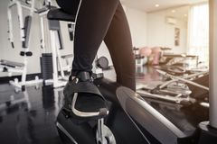 Young asian woman exercising on the xtrainer machines. In gym Stock Photos