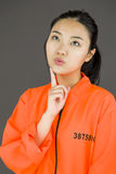 Young Asian woman with finger on chin in prisoners uniform Royalty Free Stock Photos