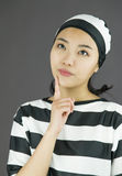 Young Asian woman with finger on chin in prisoners uniform Stock Photography