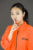 Young Asian woman with finger on lips in prisoners uniform Stock Photography