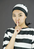 Young Asian woman with finger on lips in prisoners uniform Royalty Free Stock Images