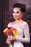 Young asian woman. With flowers portrait on wall background Stock Images