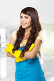 Young asian woman getting ready to do the chores, putting on yel Royalty Free Stock Photos