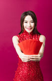 Young asian woman giving  red bags for rich Royalty Free Stock Photography