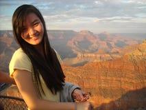 Young Asian Woman at the Grand Canyon, Arizona. A smiling young Asian woman is shown at the Grand Canyon, Arizona at sunset Royalty Free Stock Image