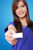 Young Asian woman handing a blank white card. Beautiful young Asian woman smiling and handing a blank white card, on vibrant blue background Royalty Free Stock Image
