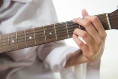 Asian woman hands touching guitar chords. Young Asian woman hands touching guitar chords stock photos