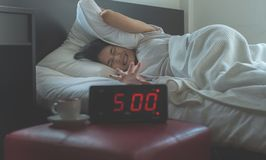 Young asian woman hates getting stressed waking up early 5 o`clock,Alarm clock. In bedroom royalty free stock photography