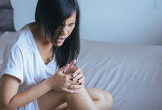 Young asian woman having a ankle pain,Female feeling exhausted and painful,Emotional face expression. Young asian woman having a ankle pain,Female feeling royalty free stock photography