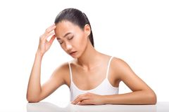 Young Asian woman having headache isolated on white background. Young Asian woman having headache. Girl siting with sickly look and closed eyes. Expression of Royalty Free Stock Photo
