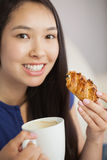 Young asian woman having a pastry with a cup of coffee Stock Image
