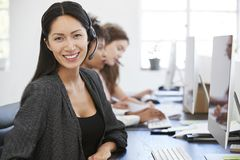 Young Asian woman with headset smiling to camera in office. Young Asian women with headset smiling to camera in office Royalty Free Stock Photos
