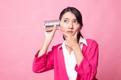 Young Asian woman hearing with tin can phone and thinking. On pink background stock photos