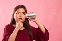 Young Asian woman hearing with tin can phone and thinking. On pink background royalty free stock images