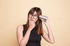 Young Asian woman hearing with tin can phone and thinking. On beige background stock image