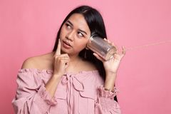Young Asian woman hearing with tin can phone and thinking. On pink background royalty free stock photography