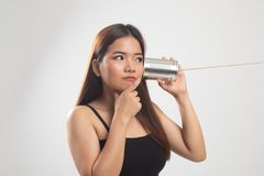 Young Asian woman hearing with tin can phone and thinking. On white background royalty free stock images