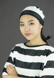 Young Asian woman with her arms crossed in prisoners uniform Stock Image