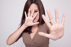 Young Asian woman hide her  face. Young Asian woman hide her  face on gray background Stock Photos