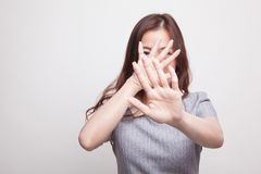 Young Asian woman hide her  face. Young Asian woman hide her  face on gray background Stock Image