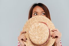 Young asian woman hiding behind a hat and looking away. Over gray background Royalty Free Stock Photos