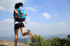 Young asian woman hiker running on mountain peak Stock Photography