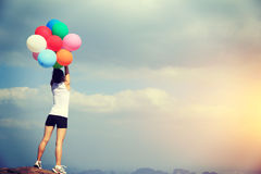 Young asian woman hold up colored balloons on mountain peak Royalty Free Stock Photos