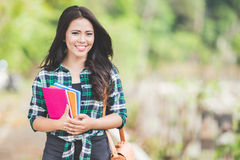 Young asian woman holding books while walking on the park Stock Photo