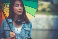 Young Asian woman holding colorful umbrella while raining. Happy Stock Photo