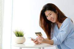 Free Young Asian Woman Holding Credit Card And Using Smart Phone For Stock Photo - 130150740