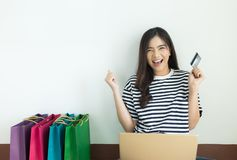 Young asian woman holding credit card and using laptop computer with shopping bags at home. Online shopping and browsing concept stock photo