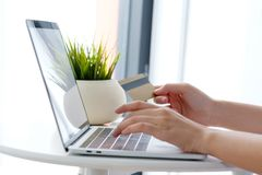 Young asian woman holding credit card and using laptop computer Royalty Free Stock Image