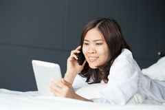 Young Asian woman holding digital tablet and phone Royalty Free Stock Images