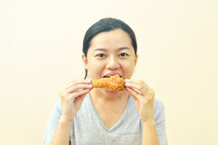 Young asian woman holding and eating fries chicken Royalty Free Stock Image