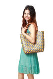 Young asian woman holding handbag. Isolated over white stock image