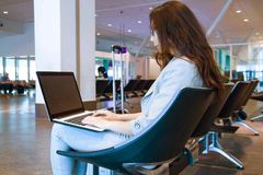 Young woman holding a laptop on lap typing keyboard indoors in airport. Young asian woman holding a laptop on lap typing keyboard indoors in airport stock photos